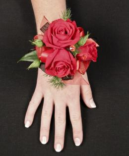 This elegant red corsage is beautiful with the hint of green, red roses and ribbon. This is great for any wedding or prom.